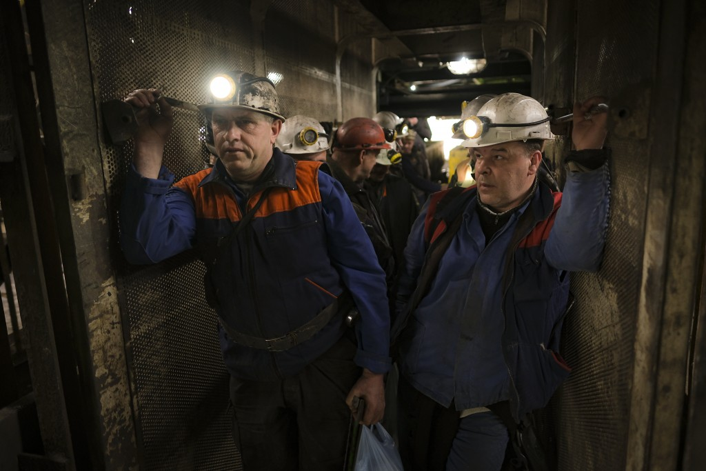 Bosnian coal miners hold bags of food as they stand in an elevator taking them underground at a mine in Zenica, Bosnia, Thursday, April 29, 2021. Duri...
