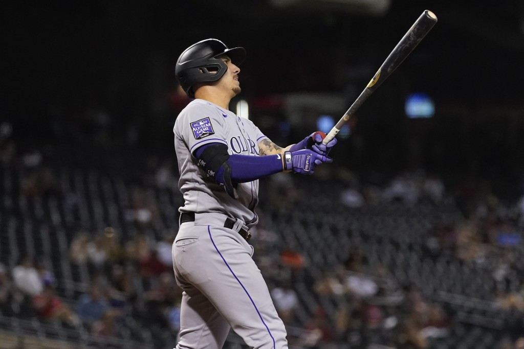 Colorado Rockies' Dom Nunez watches his grand slam home run take flight against the Arizona Diamondbacks during the eighth inning of a baseball game, ...