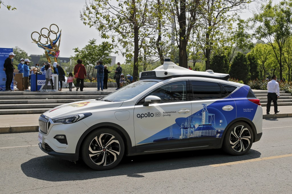 A Baidu Apollo Robotaxi passes its customer service counter setup at the Shougang Park in Beijing, Sunday, May 2, 2021. Chinese tech giant Baidu rolle...