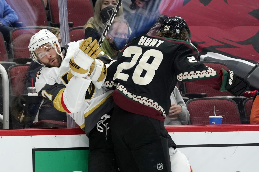 Arizona Coyotes left wing Dryden Hunt (28) checks Vegas Golden Knights defenseman Alex Pietrangelo (7) against the boards during the first period of a...