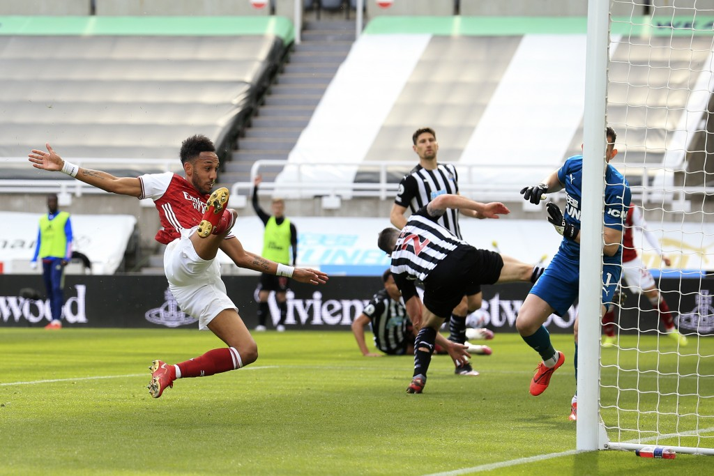 Arsenal's Pierre-Emerick Aubameyang, left, scores his side's second goal during the English Premier League soccer match between Newcastle United and A...