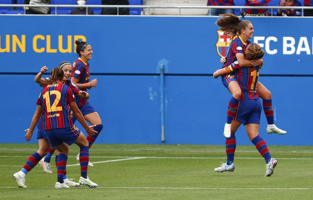 Barcelona's Lieke Martens is congratulated by teammate Alexia Putellas after scoring her second goal during the Women's Champions League semifinal sec...