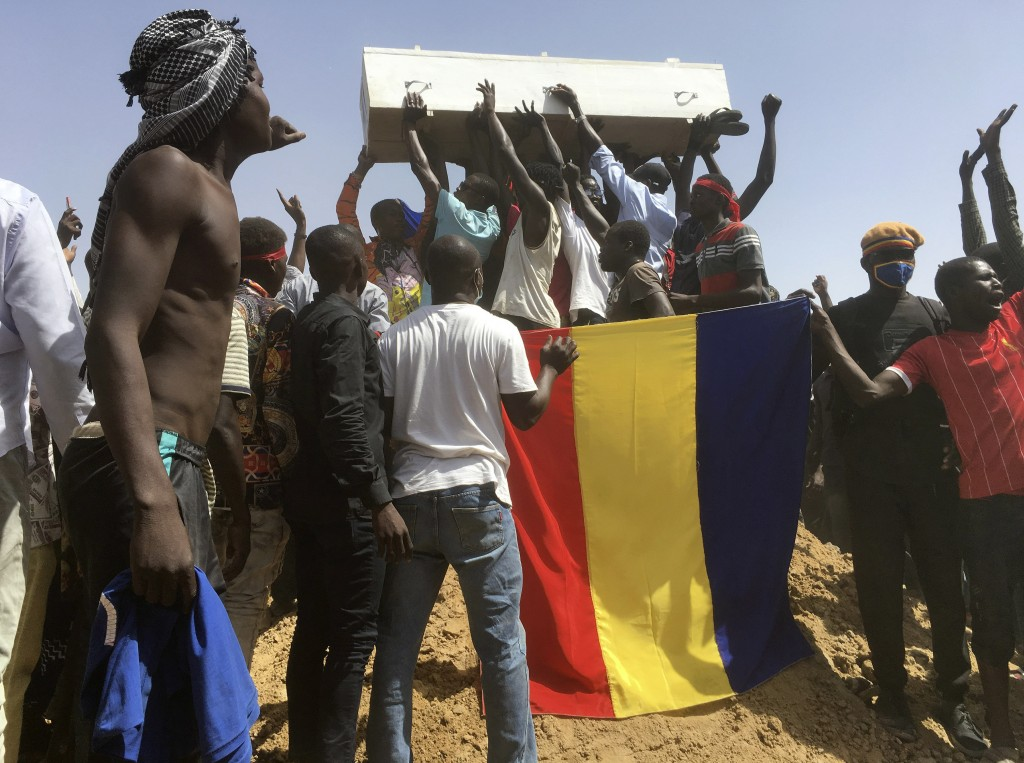 Mourners chanting as some hold the coffin during the funeral of one of the victims who was killed earlier this week, at a cemetery in N'Djamena, Chad,...