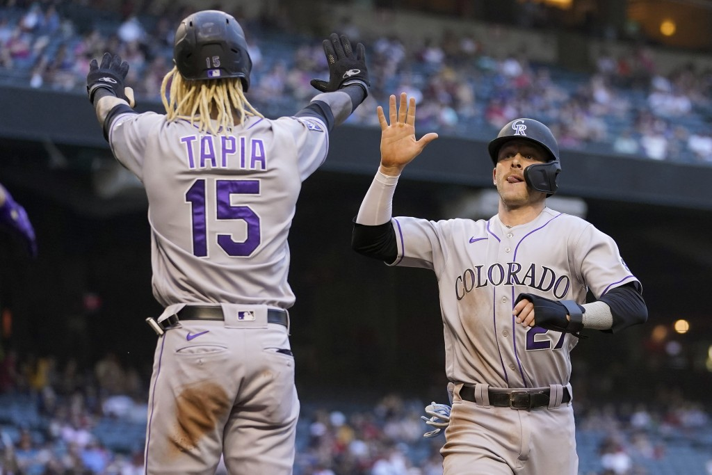 Colorado Rockies' Trevor Story (27) and Raimel Tapia (15) high five after scoring on a base hit by Ryan McMahon during the fourth inning of a baseball...