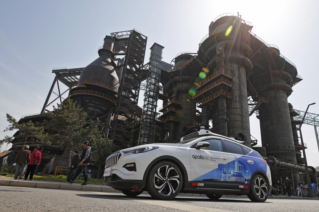 A Baidu Apollo Robotaxi move past a steel plant at the Shougang Park in Beijing, Sunday, May 2, 2021. Chinese tech giant Baidu rolled out its paid dri...