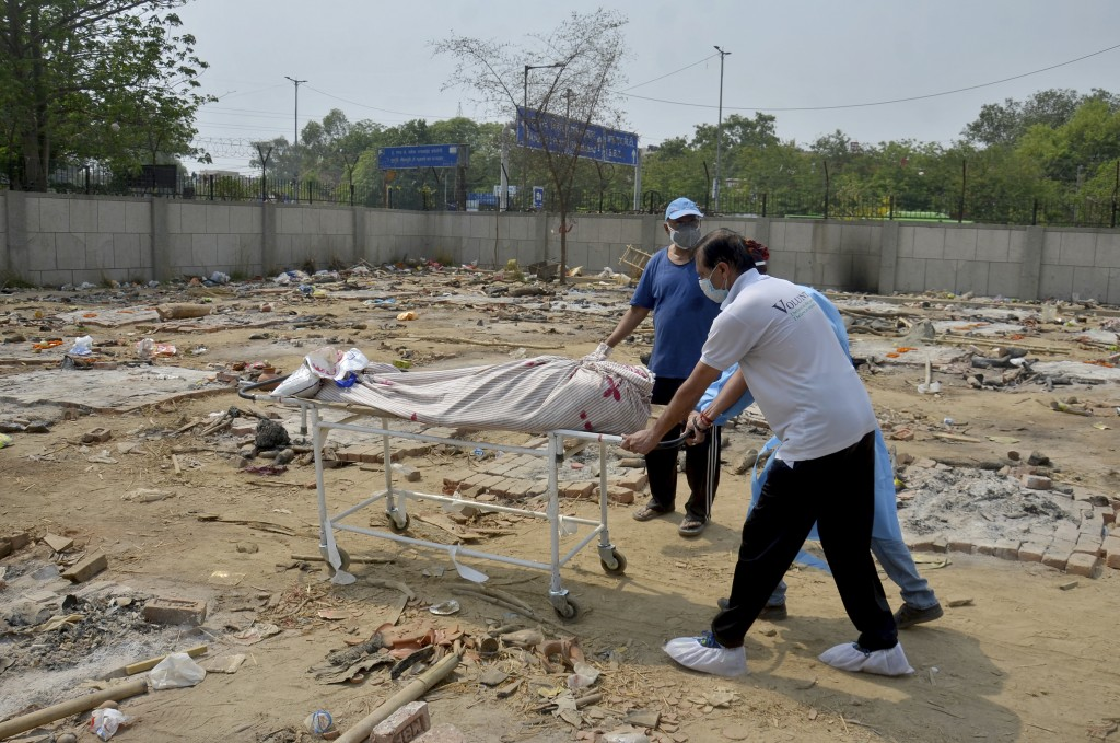Body of a COVID-19 victim is wheeled in a ground that has been converted into a crematorium in New Delhi, India, Saturday, May 1, 2021. India on Satur...