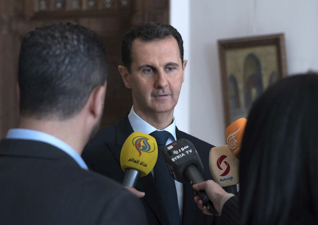 FILE - In this March 4, 2018 file photo, provided by the official Facebook page of the Syrian Presidency, Syrian President Bashar Assad speaks with re...