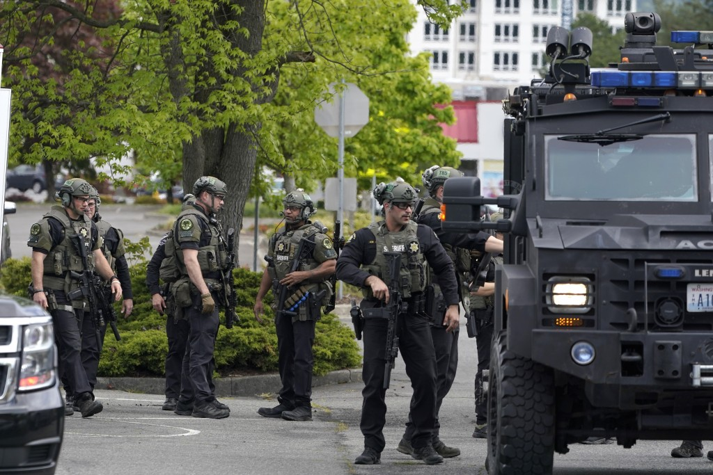 Law enforcement officers stand near an armored vehicle as they respond to a reported shooting, Saturday, May 1, 2021, at the Westfield Southcenter Mal...