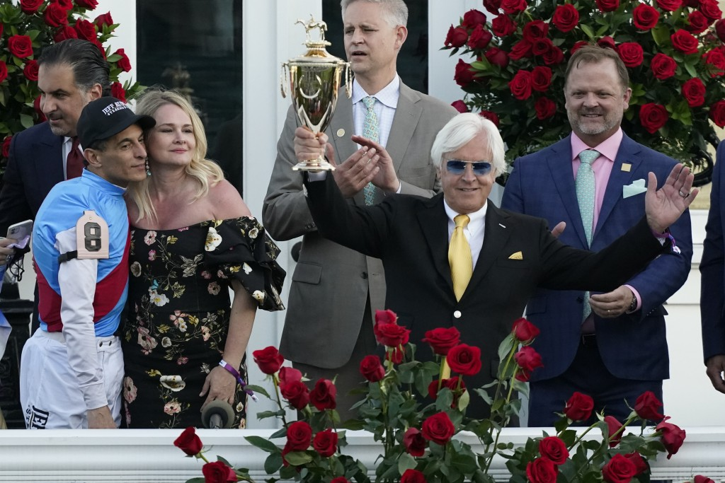 Jockey John Velazquez, left, watches as trainer Bob Baffert holds up the winner's trophy after they victory with Medina Spirit in the 147th running of...