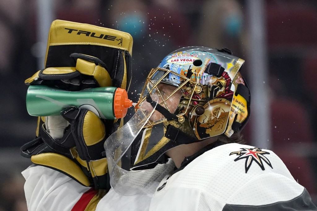 Vegas Golden Knights goaltender Marc-Andre Fleury splashes water onto his face during a break in the first period of the team's NHL hockey game agains...