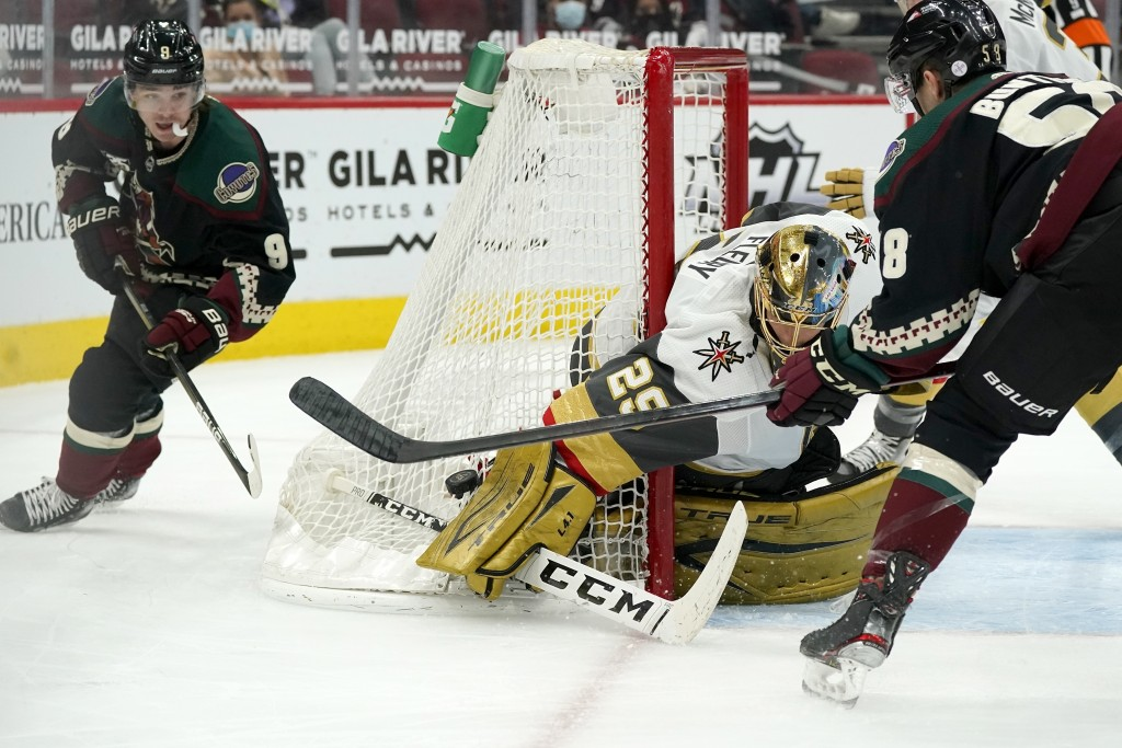 Vegas Golden Knights goaltender Marc-Andre Fleury (29) gets a glove on the puck as Arizona Coyotes right wing Clayton Keller (9) and left wing Michael...
