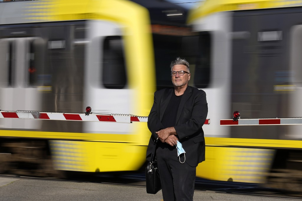 In this April 27, 2021, photo Brad Hudson poses as a Los Angeles Metro train goes by in South Pasadena, Calif. As President Joe Biden urges more feder...