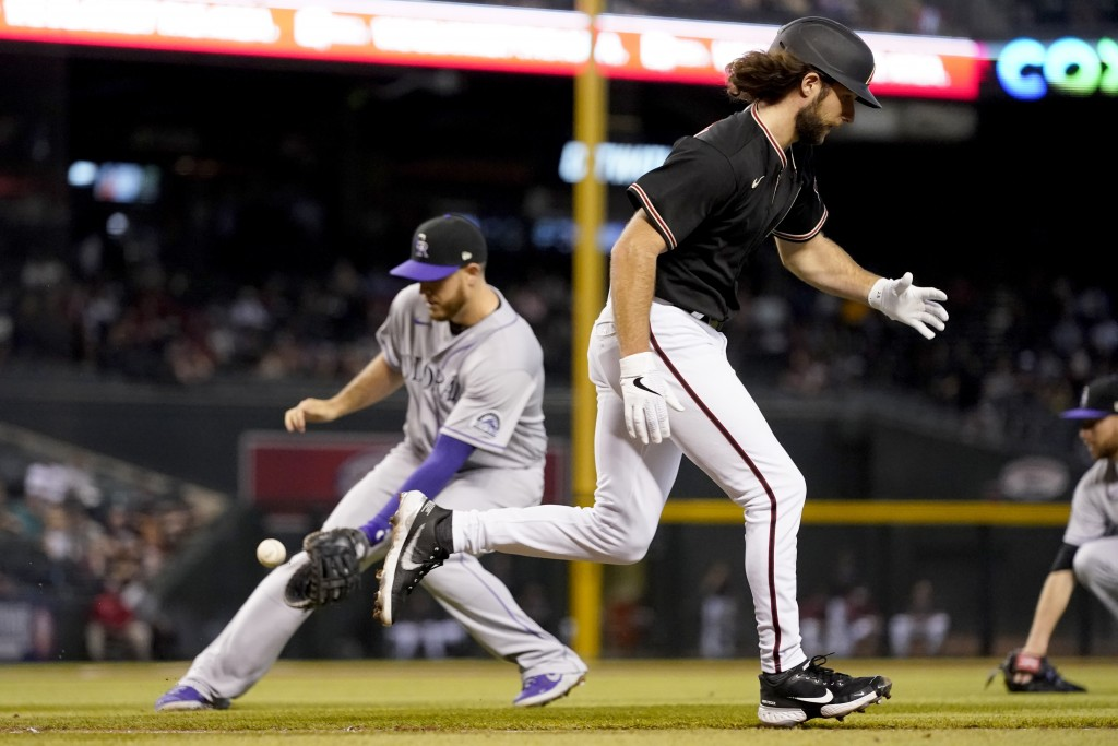 Arizona Diamondbacks' Zac Gallen, right, runs out a bunt as Colorado Rockies' C.J. Cron fields the ball for the out during the third inning of a baseb...