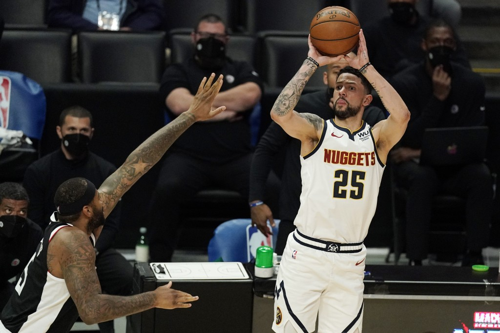 Denver Nuggets guard Austin Rivers, right, shoots as Los Angeles Clippers center DeMarcus Cousins defends during the second half of an NBA basketball ...