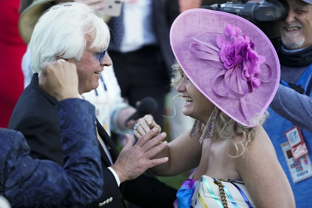 CORRECTS PERSON AT RIGHT TO LEONA O'BRIEN - Trainer Bob Baffert is greeted by Leona O'Brien, wife of jockey John Velazquez, after Medina Spirit won th...