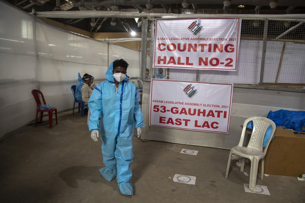A counting agent in protective suit walks past officials during the counting of votes of Assam state assembly election in Gauhati, India, Sunday, May ...