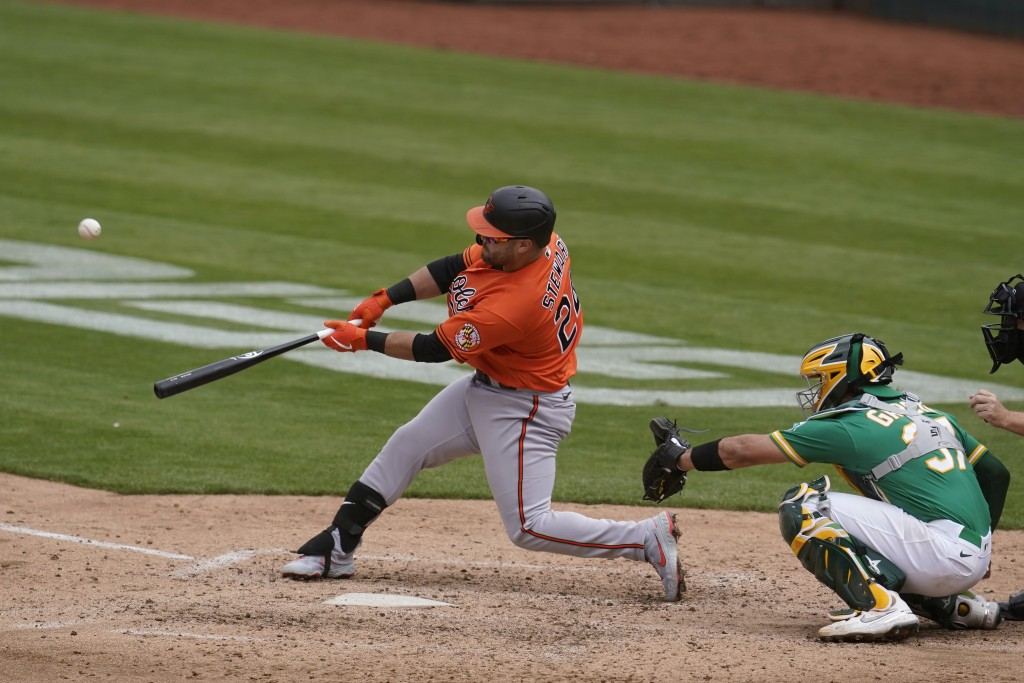 Baltimore Orioles' DJ Stewart, left, hits a two-run home run in front of Oakland Athletics catcher Aramis Garcia during the sixth inning of a baseball...