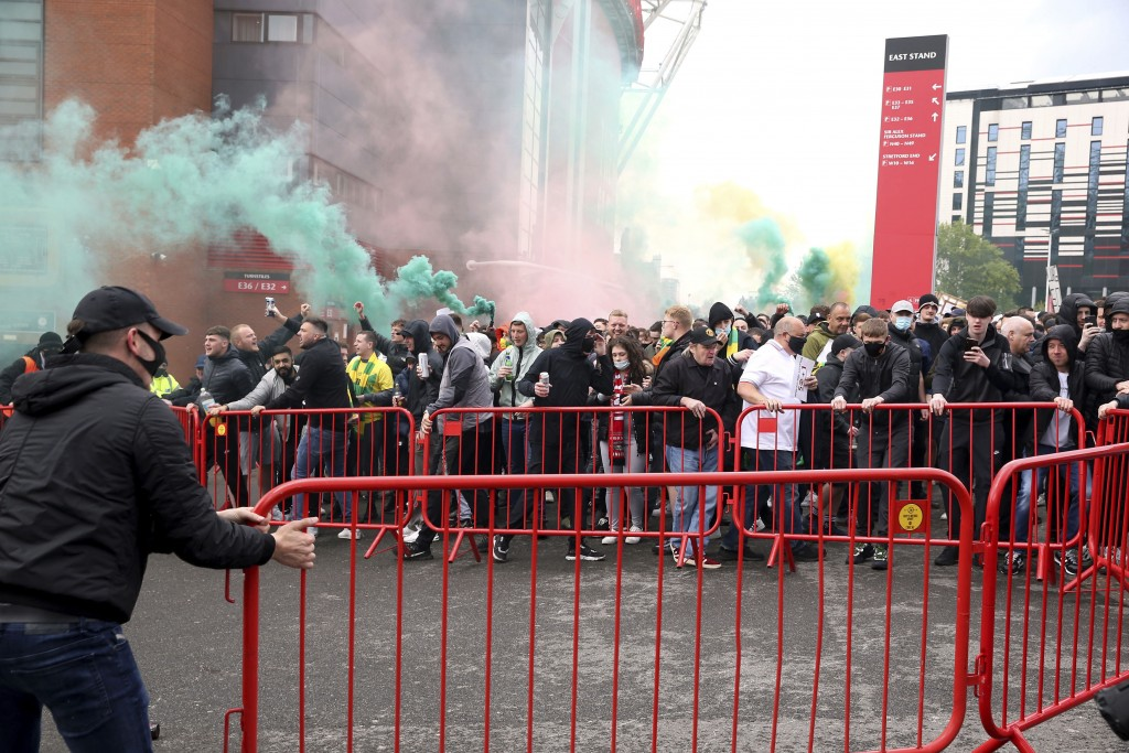 Fans move barriers outside the ground as they let off flares whilst protesting against the Glazer family, owners of Manchester United, before their Pr...