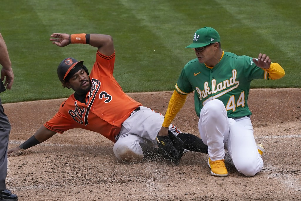 Baltimore Orioles' Maikel Franco (3) slides home to score against Oakland Athletics pitcher Jesus Luzardo (44) during the third inning of a baseball g...