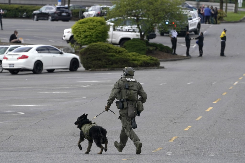 A sheriff's deputy runs with a dog in a parking lot at the Westfield Southcenter Mall after the shopping center was evacuated following a reported sho...