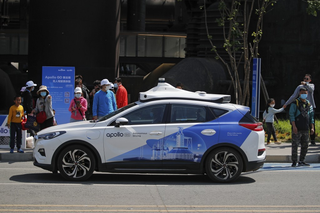 People wearing face masks look at a Baidu Apollo Robotaxi moving past a passenger pickup point setup at the Shougang Park in Beijing, Sunday, May 2, 2...
