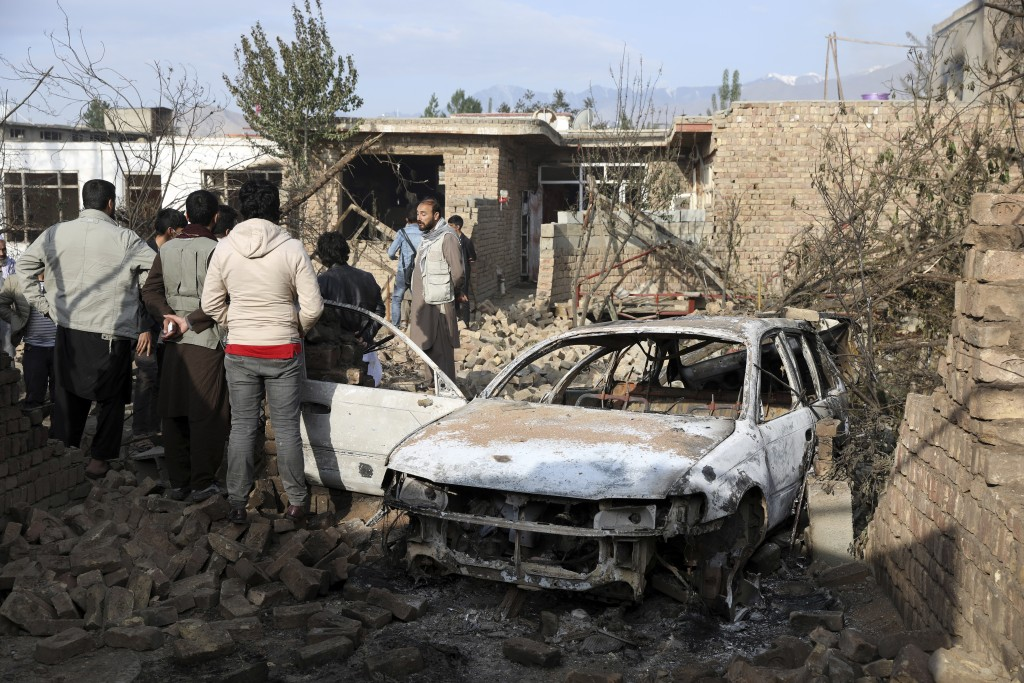Residents view vehicles and a house damaged in a fire that consumed oil tankers and trucks in Kabul, Afghanistan, Sunday, May 2, 2021. A fire roared t...