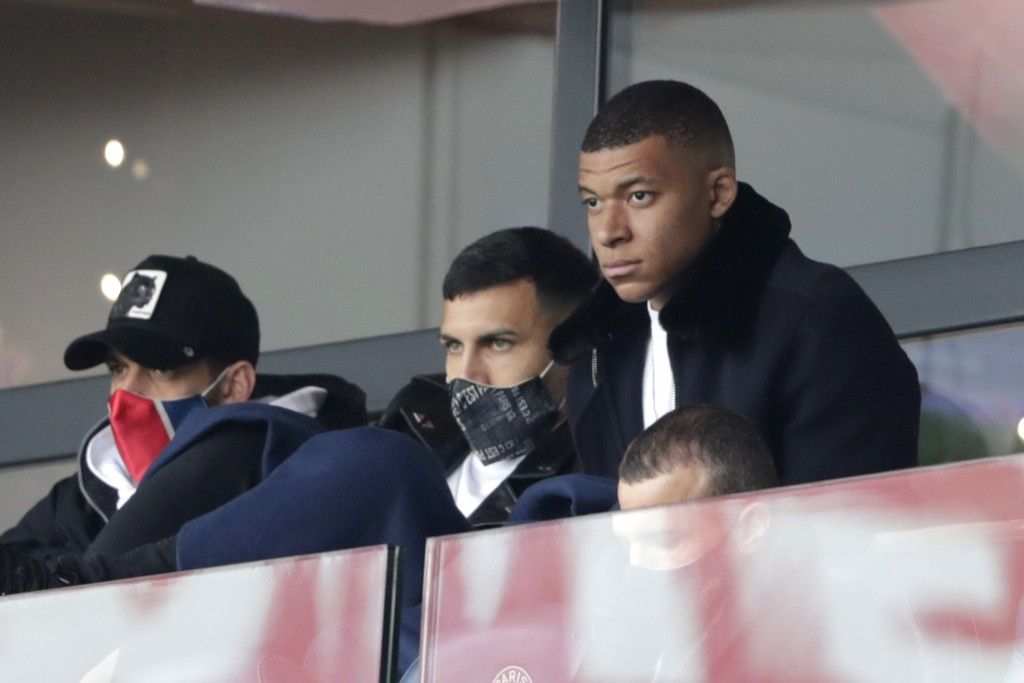 PSG's Kylian Mbappe, right, attends the French League One soccer match between Paris Saint-Germain and Lens at the Parc des Princes stadium in Paris, ...