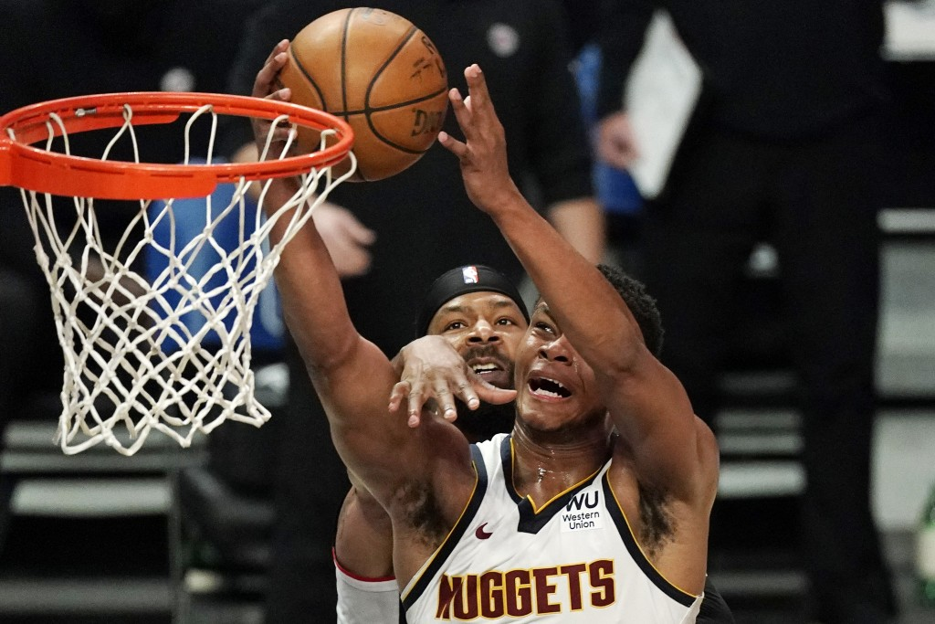 Denver Nuggets guard PJ Dozier, right, shoots as Los Angeles Clippers forward Marcus Morris Sr. defends during the second half of an NBA basketball ga...