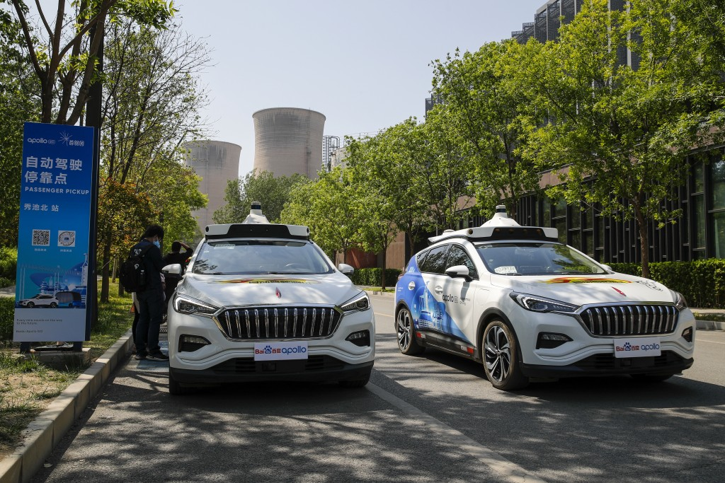 Baidu Apollo Robotaxis pass by a passenger pickup point setup at the Shougang Park in Beijing, Sunday, May 2, 2021. Chinese tech giant Baidu rolled ou...