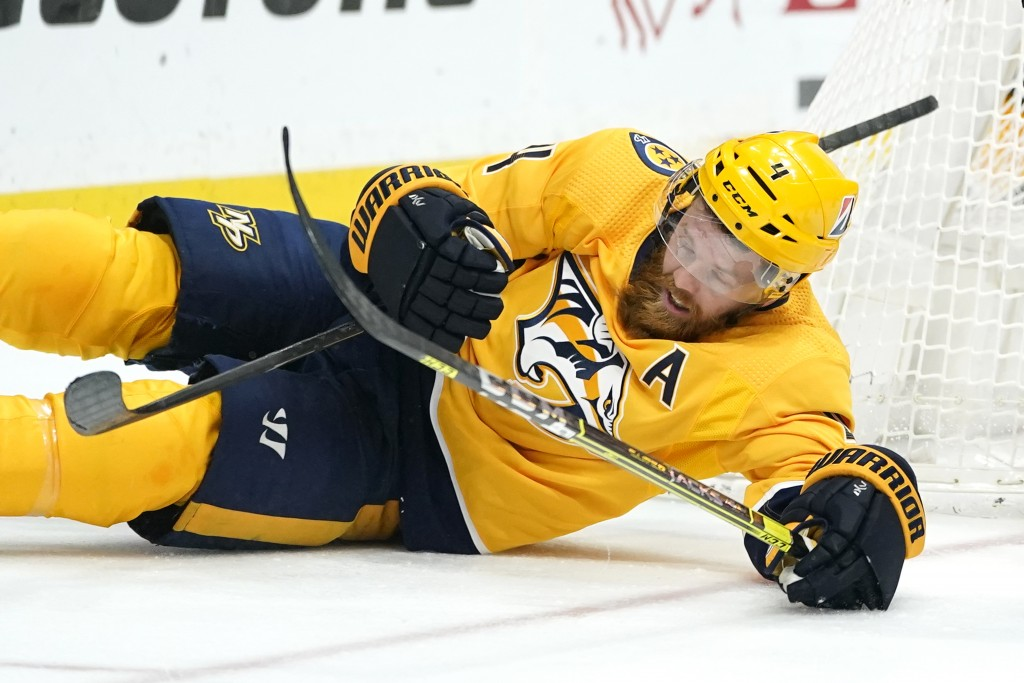 Nashville Predators defenseman Ryan Ellis (4) falls with his stick and the stick of an opponent in the third period of an NHL hockey game between the ...