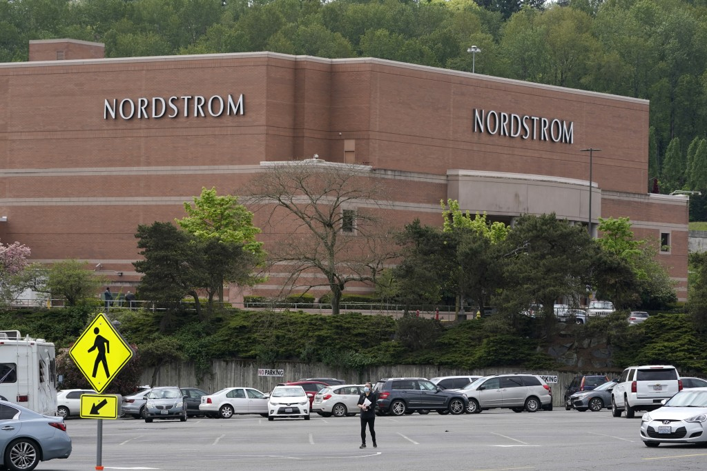 A person walks across a parking lot near a Nordstrom store at the Westfield Southcenter Mall after the shopping center was evacuated following a repor...
