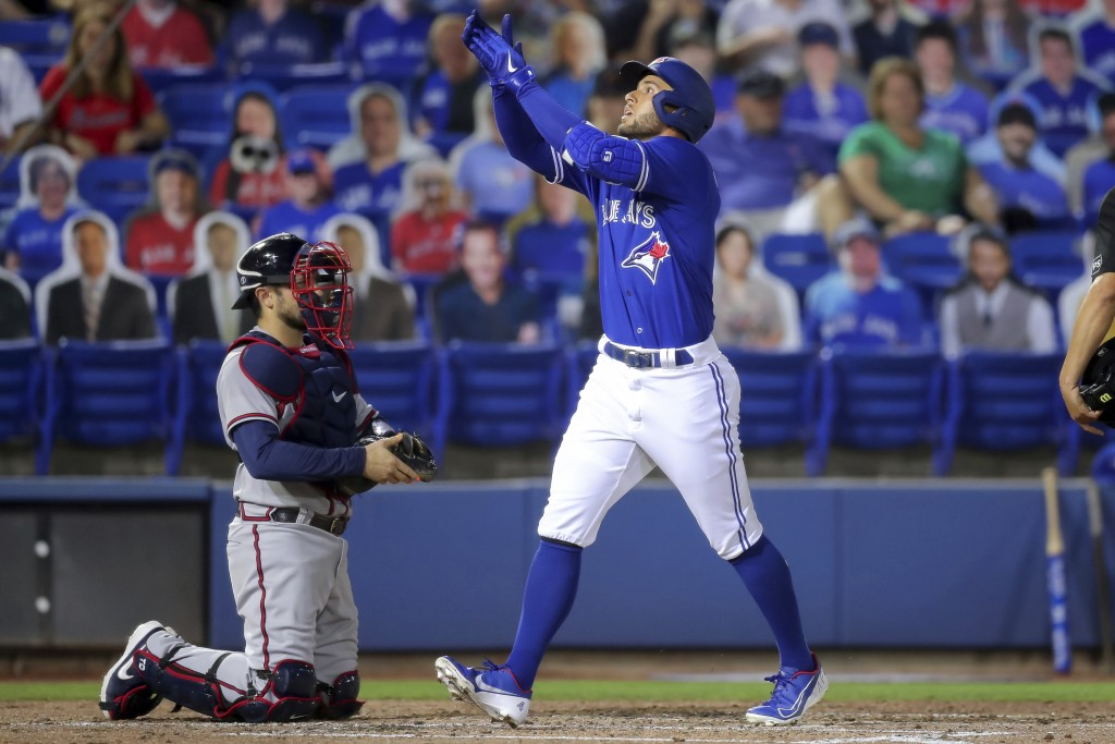 Toronto Blue Jays' George Springer celebrates as he crosses home plate in front of Atlanta Braves catcher Travis d'Arnaud after hitting a two-run home...