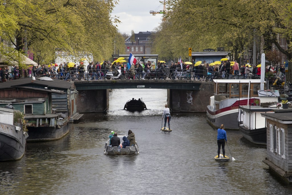 Protestors holding yellow umbrellas and the Dutch flag cross Prinsengracht canal during a demonstration against coronavirus related restrictions in Am...