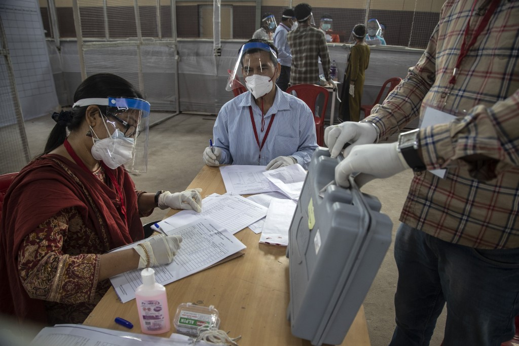 Election officials sit wearing masks and face shields during the counting of votes of Assam state assembly election in Gauhati, India, Sunday, May 2, ...