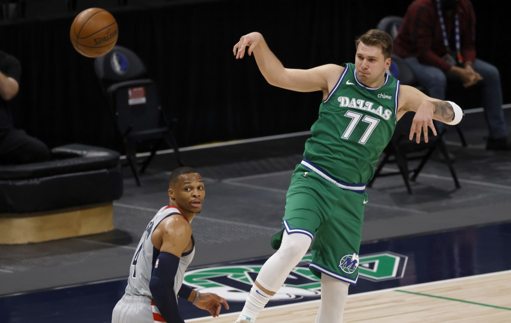Dallas Mavericks guard Luka Doncic (77) passes the ball over Washington Wizards guard Russell Westbrook (4) during the first half of an NBA basketball...