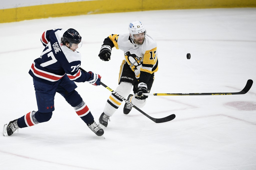 Washington Capitals right wing T.J. Oshie (77) shoots the puck next to Pittsburgh Penguins right wing Bryan Rust (17) during the second period of an N...