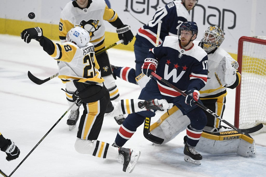 Pittsburgh Penguins defenseman Marcus Pettersson (28) reaches for the puck in front of Washington Capitals left wing Michael Raffl (17) during the sec...