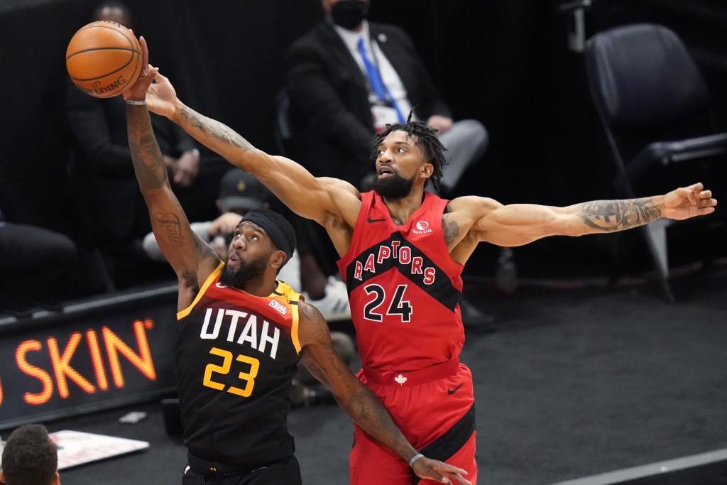Toronto Raptors center Khem Birch (24) and Utah Jazz forward Royce O'Neale (23) reach for a rebound during the first half of an NBA basketball game Sa...