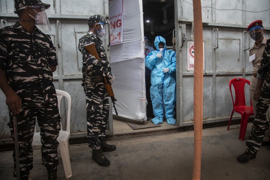 A counting agent in protective suit stands as security men guard during the counting of votes of Assam state assembly election in Gauhati, India, Sund...
