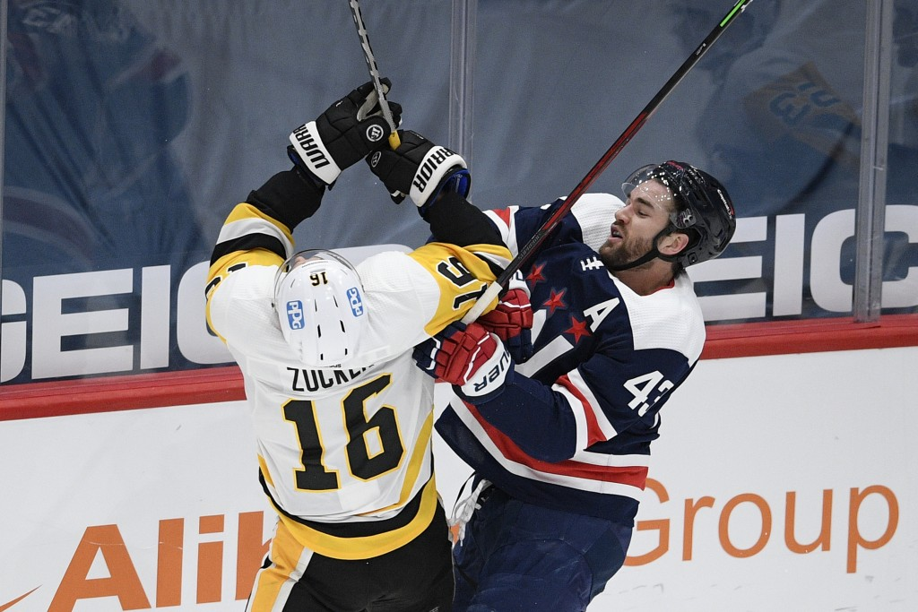 Washington Capitals right wing Tom Wilson (43) and Pittsburgh Penguins left wing Jason Zucker (16) collide during the first period of an NHL hockey ga...