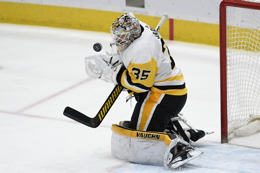 Pittsburgh Penguins goaltender Tristan Jarry stops the puck during the second period of the team's NHL hockey game against the Washington Capitals, Sa...