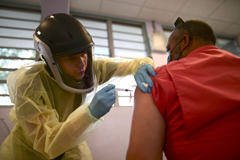 FILE - In this March 10, 2021 file photo, a healthcare worker injects a man with a dose of the Moderna COVID-19 vaccine during a mass vaccination camp...
