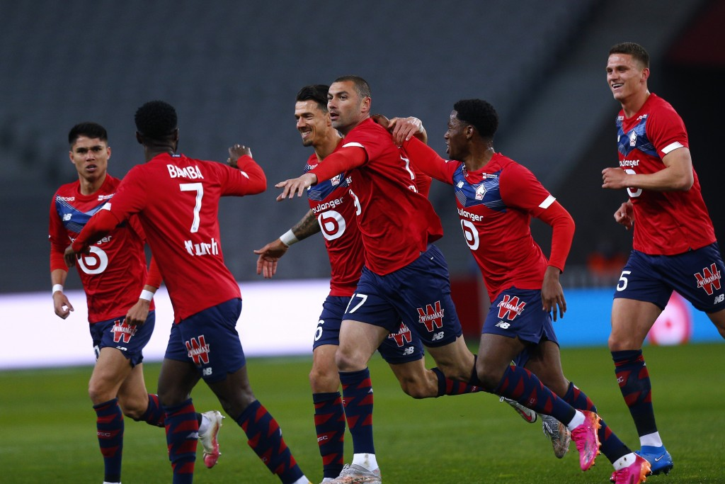 Lille's Burak Yilmaz, center, reacts with teammates after scoring during their French League One soccer match between Lille and Nice in Villeneuve d'A...