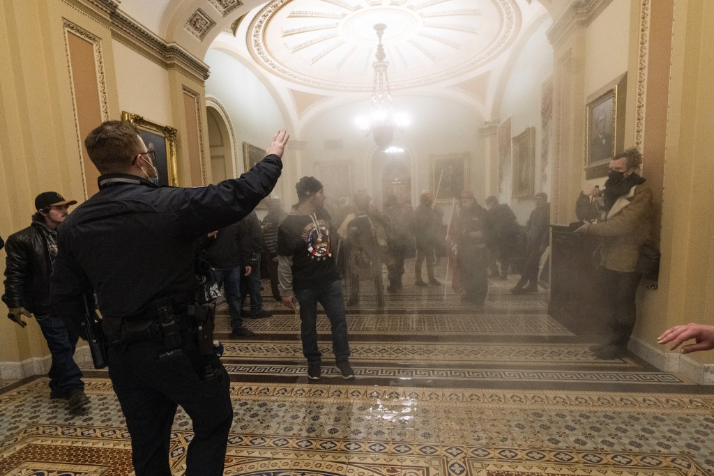 FILE - In this Jan. 6, 2021, file photo, smoke fills the walkway outside the Senate Chamber as supporters of President Donald Trump are confronted by ...