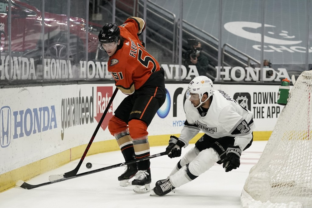 Anaheim Ducks' Haydn Fleury, left, fights for the puck with Los Angeles Kings' Andreas Athanasiou during the first period of an NHL hockey game Saturd...