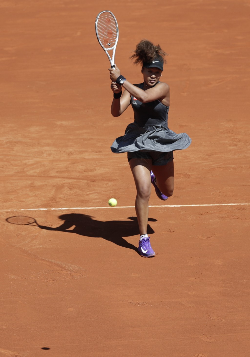 Naomi Osaka of Japan returns the ball to Karolina Muchova of the Czech Republic during their match at the Madrid Open tennis tournament in Madrid, Spa...