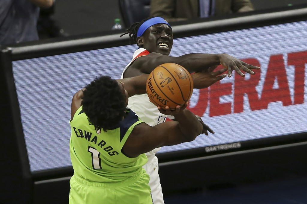Minnesota Timberwolves' Anthony Edwards (1) is fouled by New Orleans Pelicans' Wenyen Gabriel (32) while trying to shoot during the first half of an N...