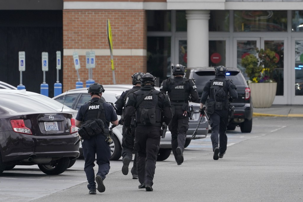 Police officers jog toward an entrance at the Westfield Southcenter Mall after the shopping center was evacuated following a reported shooting, Saturd...