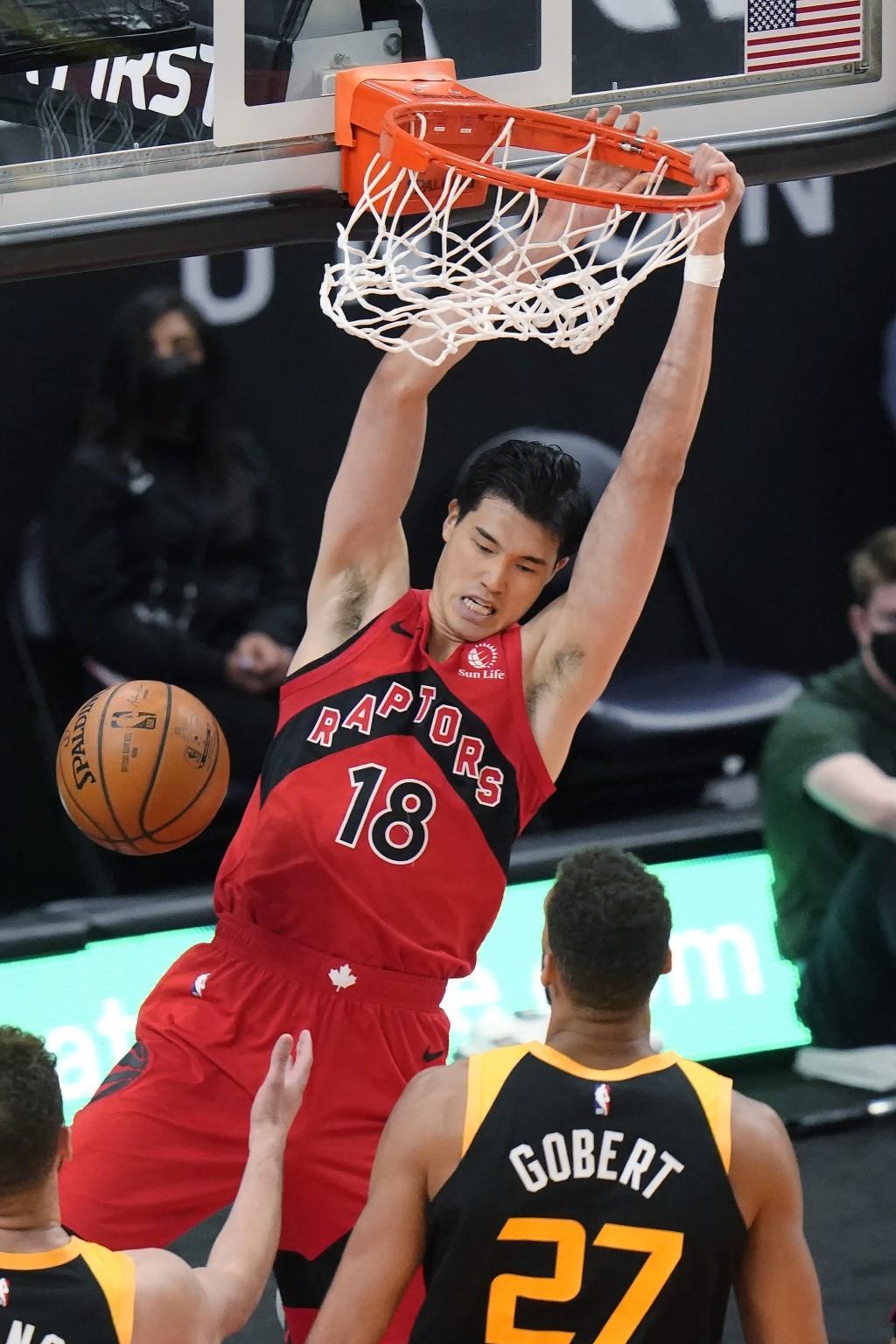 Toronto Raptors forward Yuta Watanabe (18) dunks as Utah Jazz center Rudy Gobert (27) watches during the first half of an NBA basketball game Saturday...