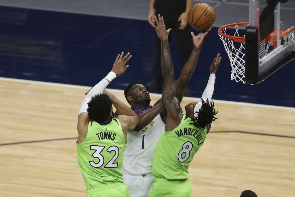 New Orleans Pelicans' Zion Williamson (1) shoots against Minnesota Timberwolves' Karl-Anthony Towns (32) and Jarred Vanderbilt (8) during the first ha...